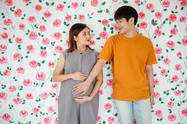 Portrait de jeune couple asiatique debout sur fond de roses blanches. un mari heureux sourit et touche le ventre de sa femme enceinte avec amour. concept de famille chaleureuse.