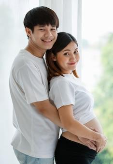 Portrait d'un jeune couple asiatique et d'une femme enceinte habillés avec désinvolture souriant et debout ensemble près de la fenêtre avec une lumière blanche et chaude de l'extérieur. notion de famille.