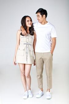 Portrait de jeune couple asiatique séduisant, homme portant un t-shirt blanc et un pantalon beige, femme portant une robe beige. bras de l'homme autour de la femme sur fond blanc. concept pour la photographie avant le mariage.