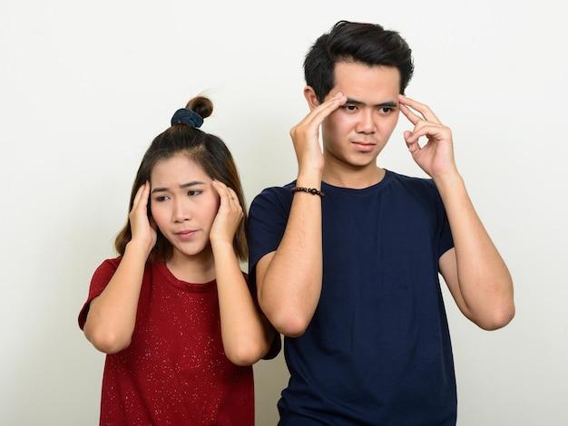 Portrait de jeune couple asiatique stressé ayant des maux de tête ensemble