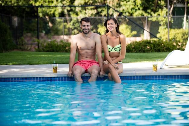 Portrait de jeune couple assis au bord de la piscine par une journée ensoleillée