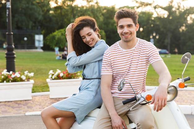 Portrait de jeune couple, assis ensemble sur une moto dans le parc de la ville