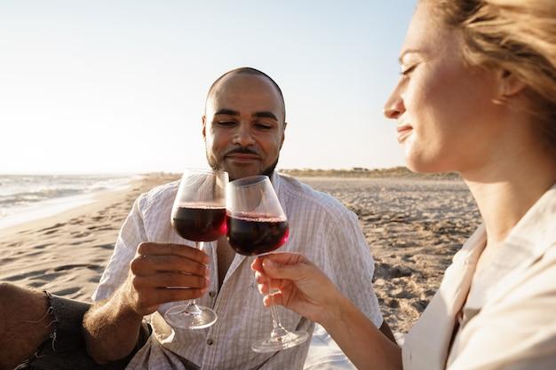 Portrait d'un jeune couple assis sur la plage et buvant du vin