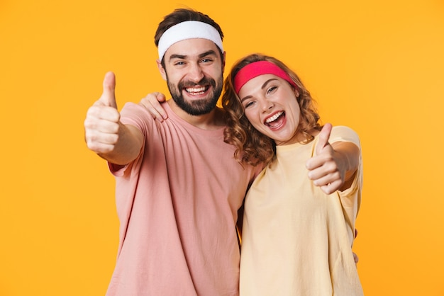 Portrait d'un jeune couple athlétique portant des bandeaux souriant et gesticulant les pouces vers le haut isolé sur jaune