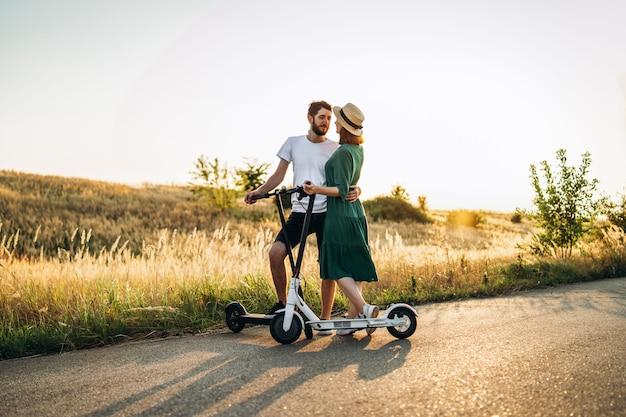 Portrait de jeune couple au coucher du soleil avec un beau paysage naturel. marcher sur des scooters électriques à la campagne