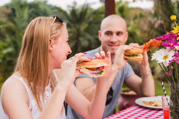 Portrait de jeune couple bénéficiant d'un sandwich à l'extérieur