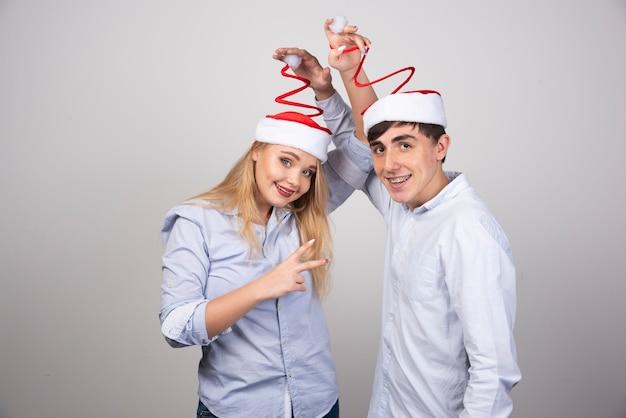 Portrait de jeune couple en bonnet de noel étant ludique sur mur gris.
