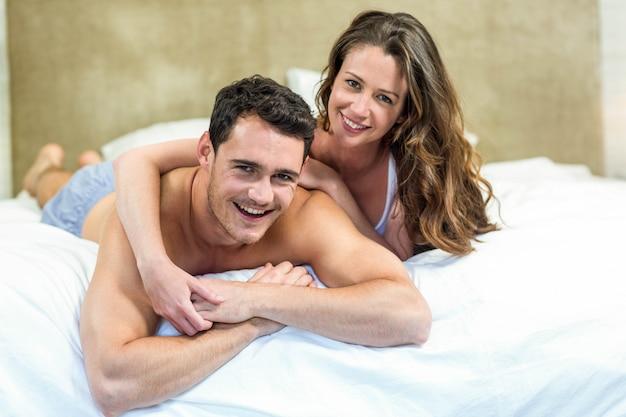 Portrait, de, jeune couple, câliner, lit, chambre à coucher