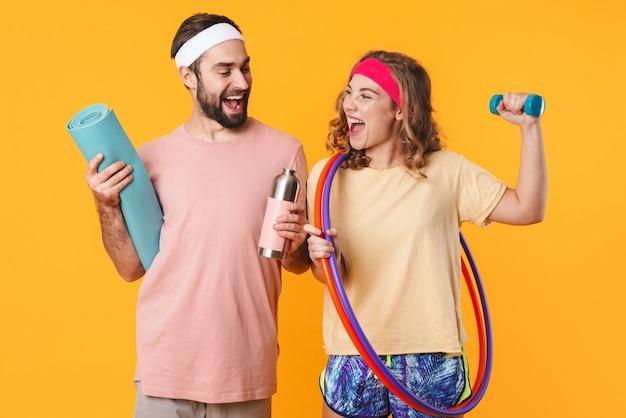 Portrait de jeune couple caucasien heureux de remise en forme portant des bandeaux souriant et tenant des équipements sportifs isolés