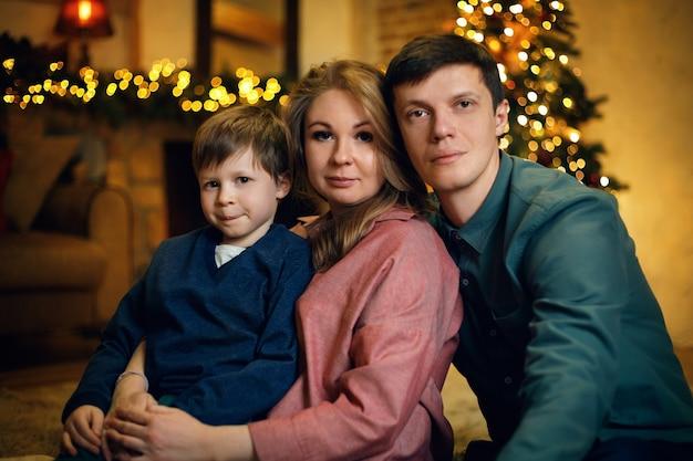 Portrait de jeune couple caucasien avec leur enfant posant sur le sol dans un intérieur de noël confortable