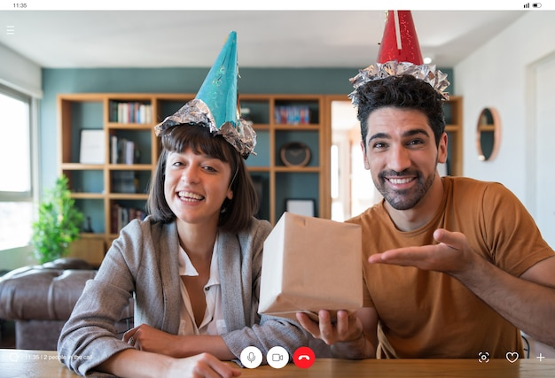 Portrait de jeune couple célébrant son anniversaire lors d'un appel vidéo avec une boîte-cadeau de la maison