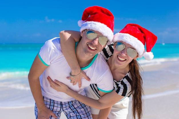 Portrait de jeune couple en chapeaux santa profiter de vacances à la plage