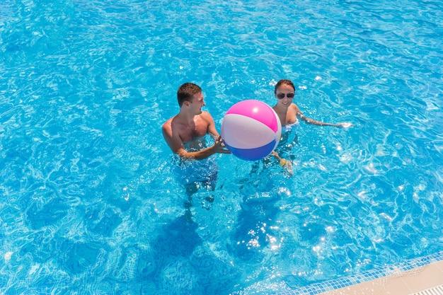 Portrait de jeune couple debout dans l'eau claire de la piscine et jouant avec un ballon de plage à rayures