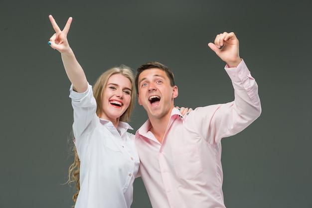 Portrait d'un jeune couple debout sur fond gris