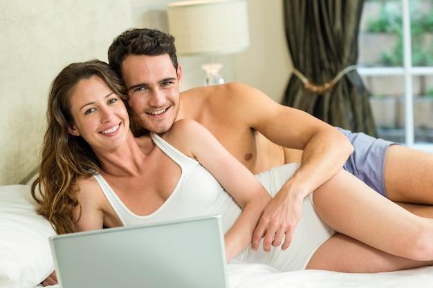 Portrait de jeune couple de détente sur le lit dans la chambre