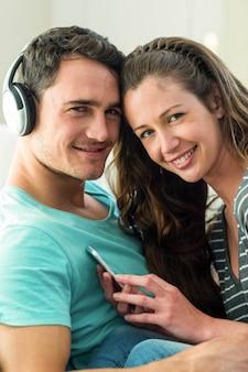 Portrait, de, jeune couple, écoute, musique, sur, téléphone portable, dans, salle de séjour
