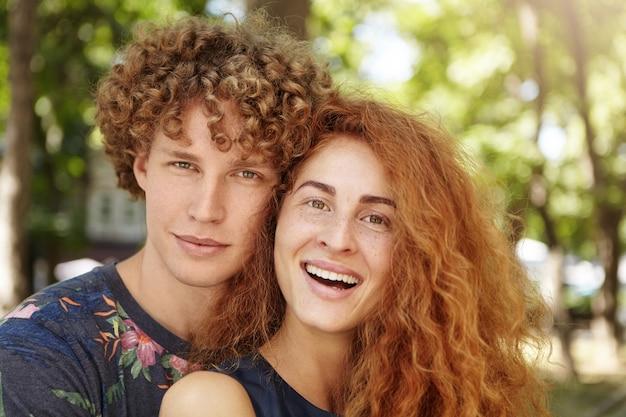 Portrait, de, jeune couple, étreindre, et, regarder appareil-photo