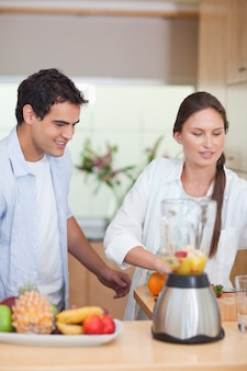 Portrait d'un jeune couple faisant des jus de fruits frais