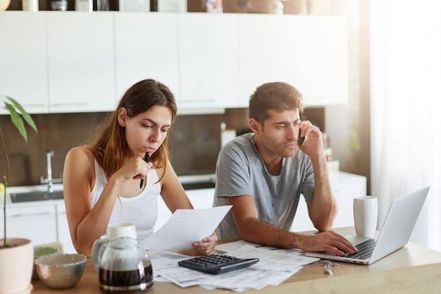 Portrait de jeune couple: femme lisant attentivement le document et homme assis devant un ordinateur portable ouvert et discutant avec un partenaire commercial sur téléphone intelligent, étant occupé à faire un rapport financier