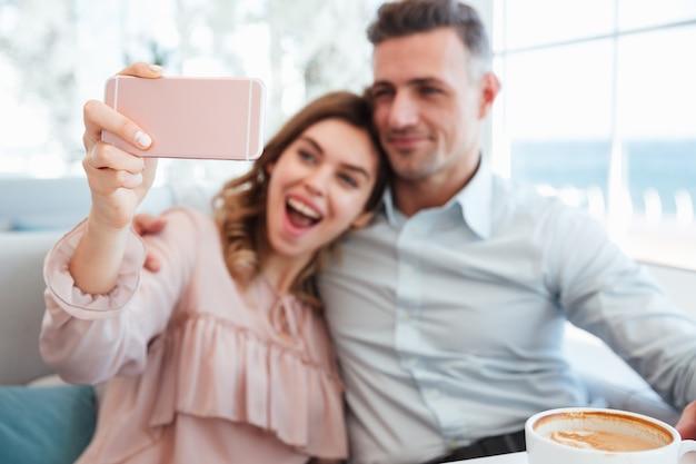 Portrait d'un jeune couple gai prenant un selfie