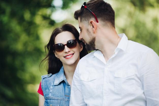 Portrait de jeune couple heureux en amour, souriant et embrassant dans le jardin