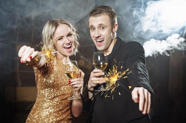 Portrait d'un jeune couple heureux avec des lunettes et des feux de bengale.