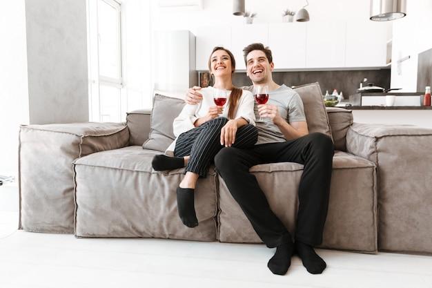 Portrait d'un jeune couple heureux se détendre sur un canapé