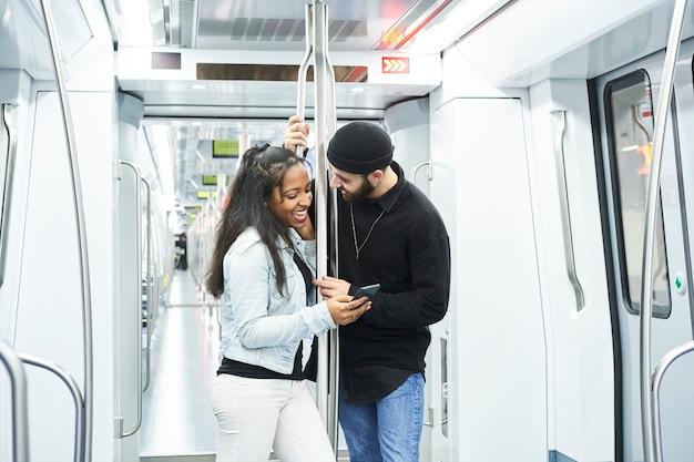 Portrait d'un jeune couple interracial dans la voiture de métro debout