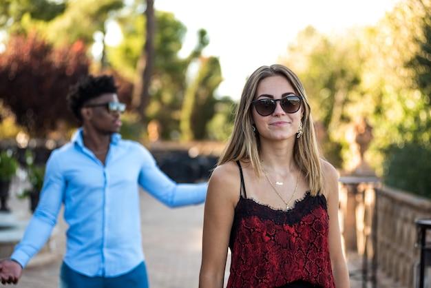 Portrait de jeune couple interracial. jeune fille avec des lunettes de soleil en premier plan.