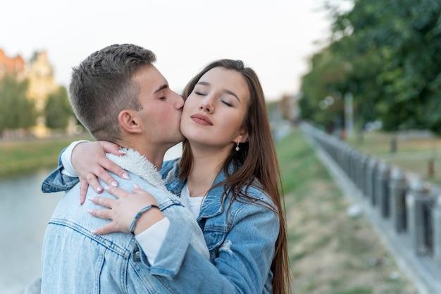 Portrait de jeune couple. jeune homme embrassant sa petite amie en plein air. doux câlins sur fond de ville. un rendez-vous romantique