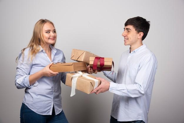 Portrait d'un jeune couple joyeux debout et se regardant tout en tenant des boîtes à cadeaux.