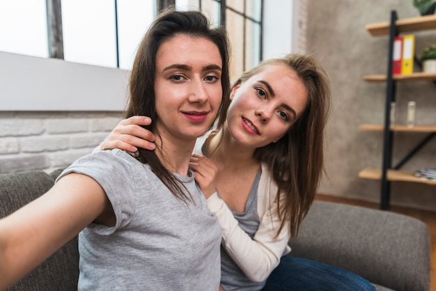 Portrait d'un jeune couple de lesbiennes souriant assis sur un canapé prenant selfie