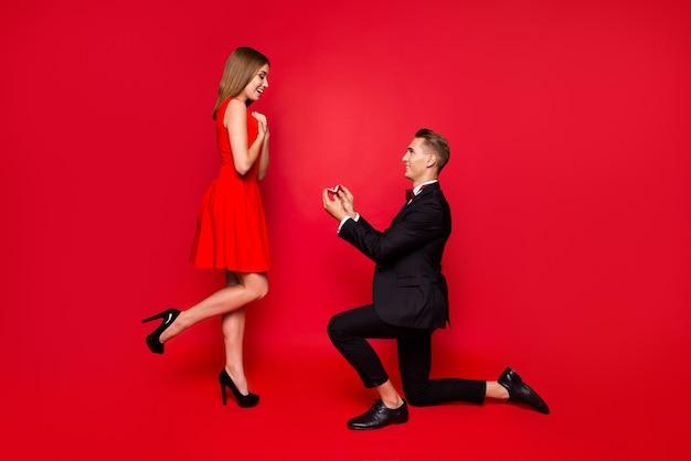 Portrait de jeune couple mignon sur fond rouge