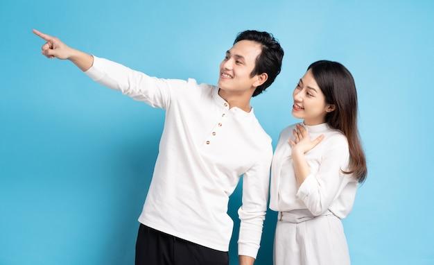 Portrait de jeune couple pointant et regardant à gauche