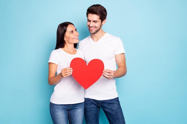 Portrait de jeune couple posant sur un mur de couleur bleue