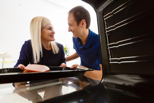 Portrait d'un jeune couple préparant la nourriture dans la cuisine. la jeune femme au foyer tient de la viande fraîchement cuite