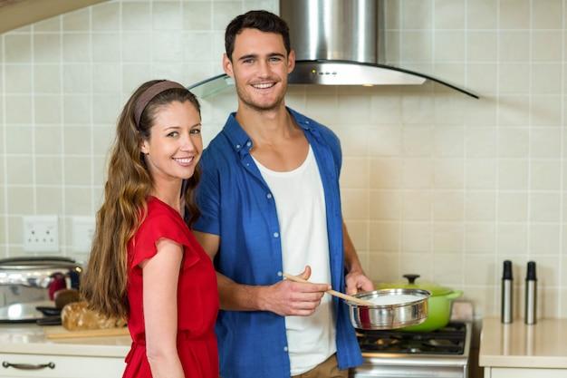 Portrait, de, jeune couple, préparer nourriture, dans, cuisine, à la maison