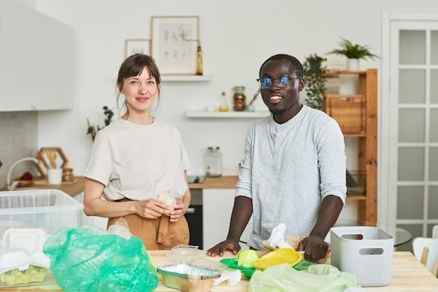 Portrait de jeune couple regardant la caméra tout en triant les ordures dans la cuisine