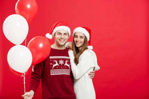 Portrait d'un jeune couple romantique avec ballon de noël sur fond de studio rouge.