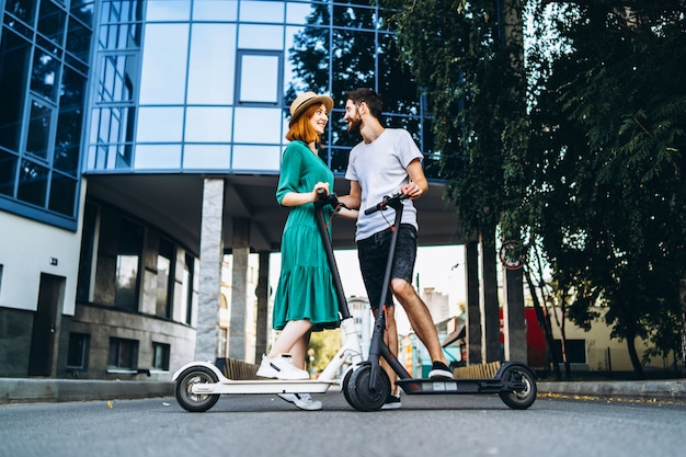 Portrait d'un jeune couple romantique avec des scooters électriques à une date, marchant dans la ville.