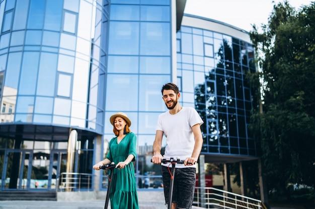 Portrait d'un jeune couple romantique avec des scooters électriques, marchant dans la ville.