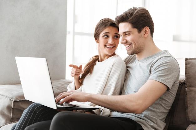 Portrait d'un jeune couple souriant à l'aide d'un ordinateur portable