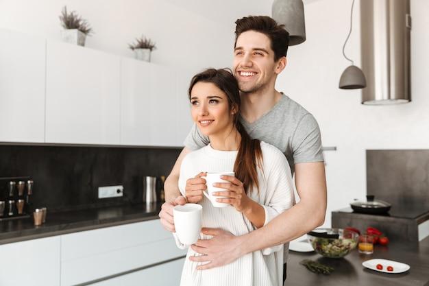 Portrait d'un jeune couple souriant, boire du café