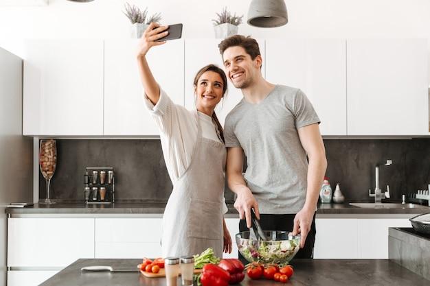 Portrait d'un jeune couple souriant prenant un selfie