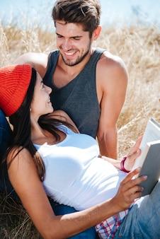 Portrait d'un jeune couple souriant s'amuser tout en se reposant à l'extérieur avec livre