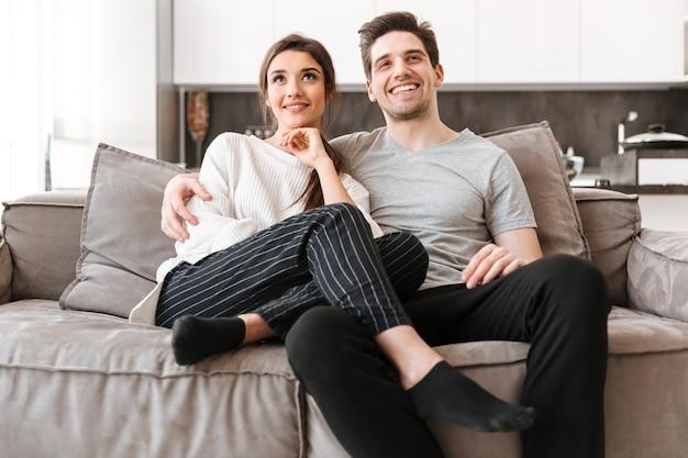 Portrait d'un jeune couple souriant se détendre sur un canapé