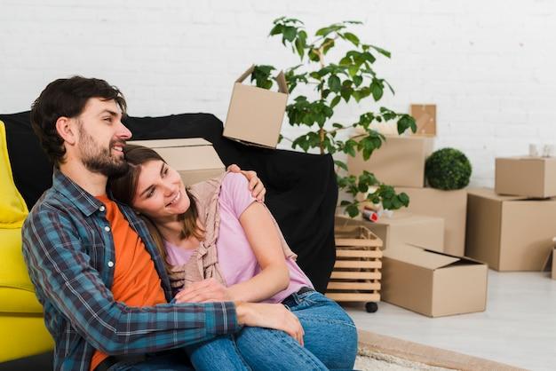 Portrait d'un jeune couple souriant se détendre dans leur nouvel appartement