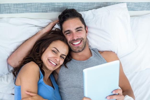 Portrait de jeune couple avec tablette en position couchée sur le lit