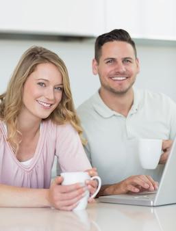 Portrait de jeune couple avec des tasses à café et un ordinateur portable assis à table dans la cuisine