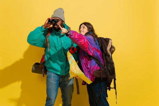 Portrait d'un jeune couple de touristes joyeux isolé sur jaune